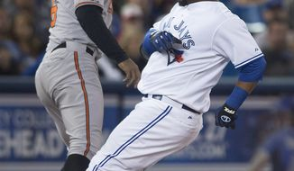 Toronto Blue Jays' Juan Francisco, right, beats the throw to Baltimore Orioles third baseman Jonathan Schoop to hit a triple during fourth inning MLB baseball action in Toronto on Tuesday, April 22, 2014. (AP Photo/The Canadian Press, Darren Calabrese)