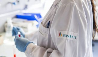 FILE - The Oct. 19, 2012 file photo shows a Novartis employee in a laboratory of Novartis in Prangins near Nyon, Switzerland. Swiss pharmaceutical giant Novartis AG announced a series of multibillion-dollar deals Tuesday, April 22, 2014 with other major pharmaceutical companies that it said would reduce sales but boost profitability, while affecting some 15,000 of its employees globally.  (AP Photo/Keystone, Yannick Bailly)
