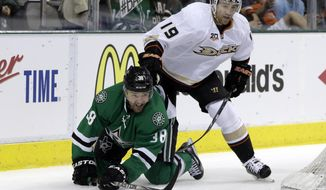Dallas Stars' Vernon Fiddler (38) fights off pressure from Anaheim Ducks' Stephane Robidas (19) as the two chase a loose puck in the first period of Game 3 of a first-round NHL hockey Stanley Cup playoff series game, Monday, April 21, 2014, in Dallas. (AP Photo/Tony Gutierrez)