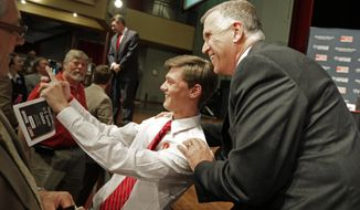 "Republican senatorial candidate Thom Tillis, right, has a ""selfie"" taken with a supporter before a debate at Davidson College in Davidson, N.C., Tuesday, April 22, 2014. (AP Photo/Chuck Burton)"
