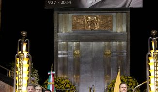 Colombia's President Juan Manuel Santos, left, and Mexico's President Enrique Pena Nieto, stand next to the urn containing the ashes of Colombian Nobel Literature laureate Gabriel Garcia Marquez during the authors homage at the Palace of Fine Arts in Mexico City, Monday, April 21, 2014. Garcia Marquez died on Thursday at his home in Mexico City. His magical realist novels and short stories exposed tens of millions of readers to Latin America's passion, superstition, violence and inequality. (AP Photo/Eduardo Verdugo)