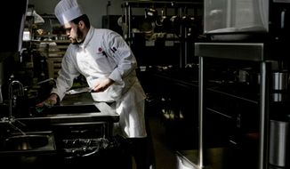 In this photo taken on Thursday, April 17, 2014, Shawn Kraft sanitizes a surface before preparing a dish at the Courses restaurant at Baker College Culinary Institute of Michigan in Port Huron, Mich. Courses provides students hands-on experience with a restaurant environment (AP Photo/The Port Huron Times Herald, )Jeffrey Smith  NO SALES