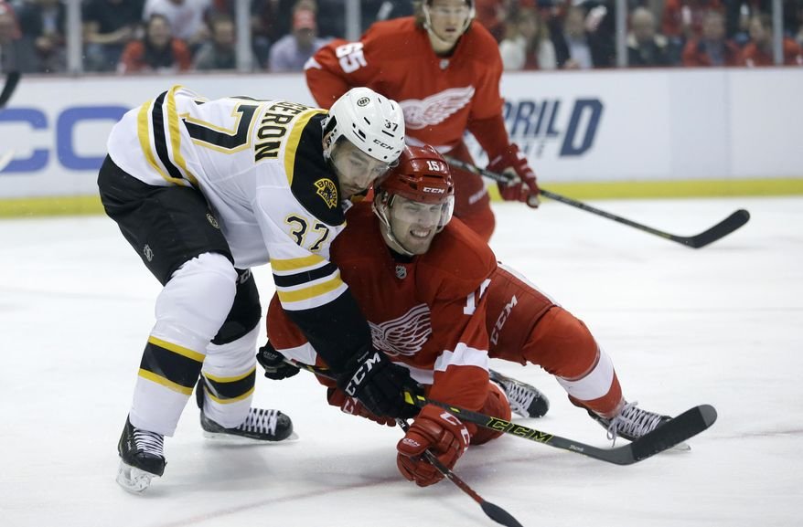 Boston Bruins center Patrice Bergeron (37) and Detroit Red Wings center Riley Sheahan (15) battle for the puck during the first period of Game 3 of a first-round NHL hockey playoff series in Detroit, Tuesday, April 22, 2014. (AP Photo/Carlos Osorio)