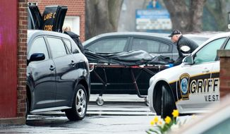In this photo taken April 21, 2014, a body bag is rolled into a coroner's van at the scene of a fatal shooting in the parking lot at St. Mary's School in Griffith, Ind. Nina Castro, 42, was shot to death by her estranged husband, Remanard Castro, 55, who later died of a self-inflicted gunshot wound at his home after a police officer confronted him, police said. (AP Photo/The Times, Kyle Telechan) MANDATORY CREDIT; CHICAGO LOCALS OUT;  GARY OUT.