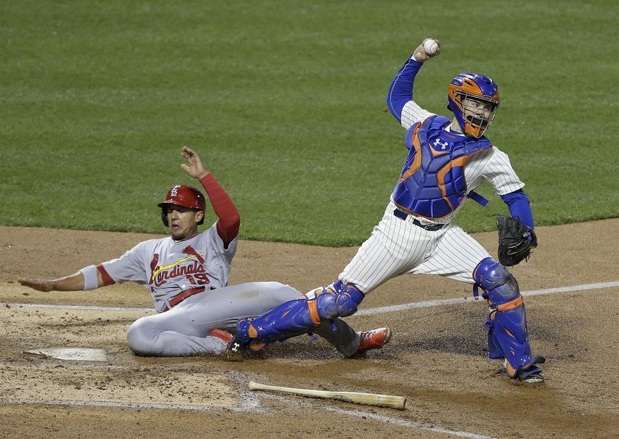 St. Louis Cardinals' Jon Jay (19) slides into New York Mets catcher Travis d'Arnaud after being tagged out at home plate during the fourth inning of a baseball game Tuesday, April 22, 2014, in New York. (AP Photo/Frank Franklin II)