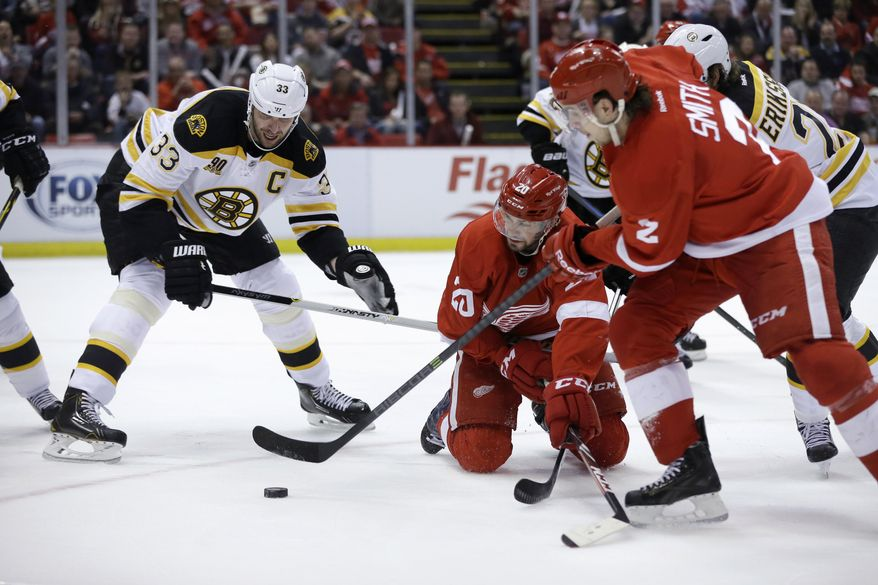 Detroit Red Wings defenseman Brendan Smith (2) controls the puck in front of teammate Drew Miller (20) and Boston Bruins defenseman Zdeno Chara (33) of the Czech Republic, during the second period of Game 3 of a first-round NHL hockey playoff series in Detroit, Tuesday, April 22, 2014. (AP Photo/Carlos Osorio)