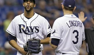 Tampa Bay Rays starting pitcher David Price, left, reacts to third baseman Evan Longoria after Price was hit in the groin on a single by Joe Mauer during the fourth inning of a baseball game Tuesday, April 22, 2014, in St. Petersburg, Fla. Price was able to remain in the game. (AP Photo/Chris O'Meara)