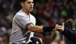 New York Yankees' Jacoby Ellsbury receives a fist-bump after scoring on a single by Derek Jeter during the fifth inning of a baseball game against the Boston Red Sox at Fenway Park in Boston, Tuesday, April 22, 2014. (AP Photo/Elise Amendola)