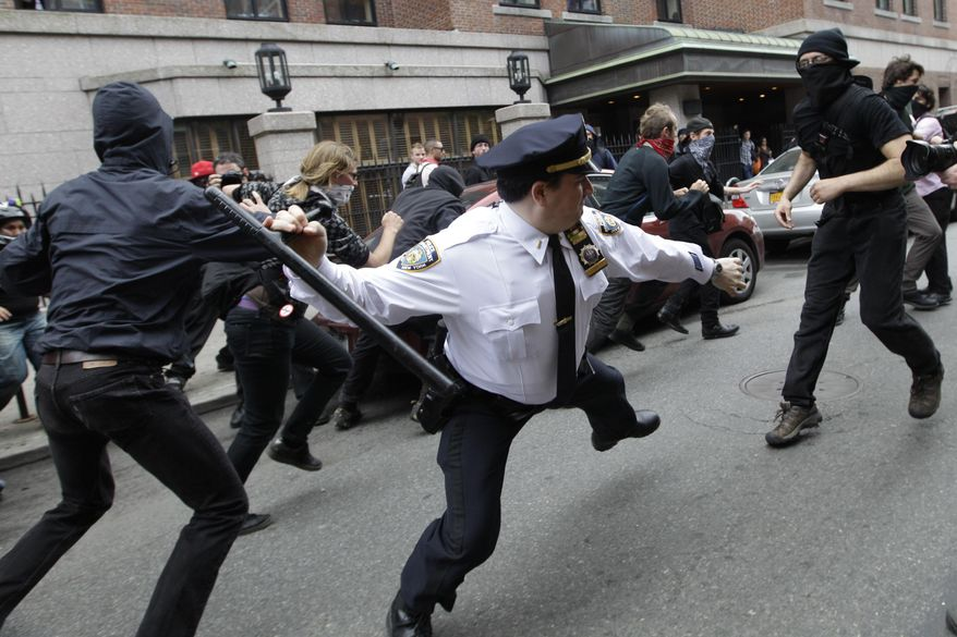 A police lieutenant swings his baton at Occupy Wall Street activists in New York, in this May 1, 2012, file photo. (AP Photo/Mary Altaffer, File)