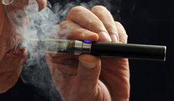 FILE - In this Jan. 17, 2014 file photo, a smoker demonstrates an e-cigarette in Wichita Falls, Texas. Soon, the Food and Drug Administration will propose rules for e-cigarettes. The rules will have big implications for a fast-growing industry and its legions of customers. (AP Photo/Wichita Falls Times Record News, Torin Halsey, File)