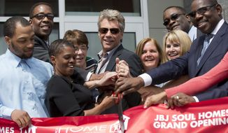 Jon Bon Jovi, center, takes part in a ribbon cutting ceremony during the grand opening of the JBJ Soul Homes, Tuesday, April 22, 2014, in Philadelphia. On Tuesday, Bon Jovi attended the grand opening of a low-income housing development that bears his initials. The 55-unit JBJ Soul Homes will be occupied by low-income tenants and the formerly homeless. Bon Jovi's Soul Foundation and the Middleton Partnership provided the lead gift for the $16.6 million complex in the Francisville neighborhood. The project also received public funds. (AP Photo/Matt Rourke)