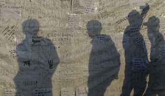 Visitors reading messages wishing safe return of missing passengers aboard the sunken ferry Sewol are silhouetted on the side of a tent at a port in Jindo, south of Seoul, South Korea, Tuesday, April 22, 2014. One by one, coast guard officers carried the newly arrived bodies covered in white sheets from a boat to a tent on the dock of this island, the first step in identifying a sharply rising number of corpses from the South Korean ferry that sank nearly a week ago. (AP Photo/Lee Jin-man)
