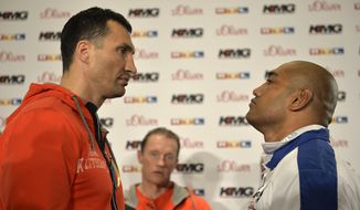 Boxing champion Wladimir Klitschko of Ukraine, left, stares at challenger Alex Leapai from Australia-Samoa during a press conference ahead of their IBF, IBO, WBO and WBA heavyweight title bout in Duesseldorf, Germany, Tuesday, April 22, 2014. (AP Photo/Martin Meissner)