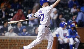 Chicago Cubs' Travis Wood watches his three-run home run against the Arizona Diamondbacks during the second inning of a baseball game on Monday, April 21, 2014, in Chicago. (AP Photo/Andrew A. Nelles)
