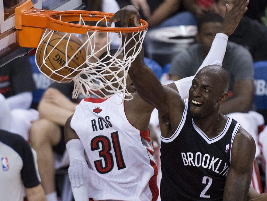Brooklyn Nets forward Kevin Garnett, right, dunks against the Toronto Raptors during the second half of Game 2 in an NBA basketball first-round playoff series, Tuesday, April 22, 2014, in Toronto. (AP Photo/The Canadian Press, Nathan Denette)