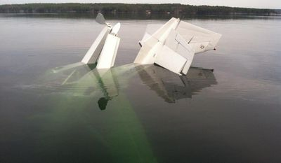 In this photo provided by the New Hampshire State Police, a small plane lies partially submerged after crashing in New Hampshire's Lake Winnipesaukee, Tuesday, April 22, 2014. New Hampshire State Police say the pilot, who was found submerged in water and clinging to the plane, was the only occupant and was rescued. (AP Photo/New Hampshire State Police)