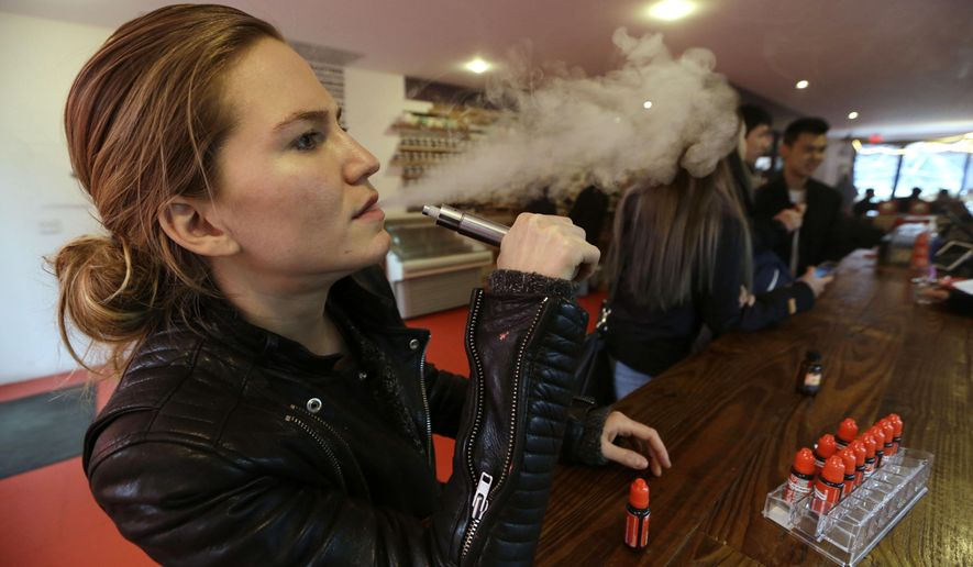 ** FILE ** Talia Eisenberg, co-founder of the Henley Vaporium, uses her vaping device in New York, Feb. 20, 2014.  (AP Photo/Frank Franklin II, File)