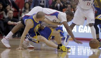 Los Angeles Clippers guard Chris Paul, top, goes over Golden State Warriors guard Steve Blake for a loose ball during the first half in Game 2 of an opening-round NBA basketball playoff series in Los Angeles, Monday, April 21, 2014. (AP Photo/Chris Carlson)
