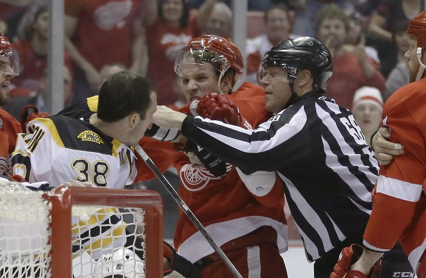 A referee breaks up Boston Bruins left wing Jordan Caron (38) and Detroit Red Wings left wing Justin Abdelkader during the first period of Game 3 of a first-round NHL hockey playoff series in Detroit, Tuesday, April 22, 2014. (AP Photo/Carlos Osorio)