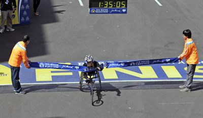 Tatyana McFadden, of the United States, breaks the tape to win the women's wheelchair division of the 118th Boston Marathon Monday, April 21, 2014 in Boston. (AP Photo/Charles Krupa)