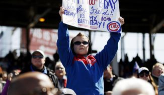 Jake Schrum, 10, of Cedar Lake, Ind., holds a sign during the fifth inning of a baseball game between the Chicago Cubs and the Arizona Diamondbacks at Wrigley Field in Chicago on Wednesday, April 23, 2014. (AP Photo/Andrew A. Nelles)