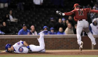 Chicago Cubs' Justin Ruggiano slides into third base after being tagged out by Arizona Diamondbacks third baseman Eric Chavez (12), during the eighth inning of a baseball game in Chicago, Tuesday, April 22, 2014. Chicago won 9-2. (AP Photo/Paul Beaty)