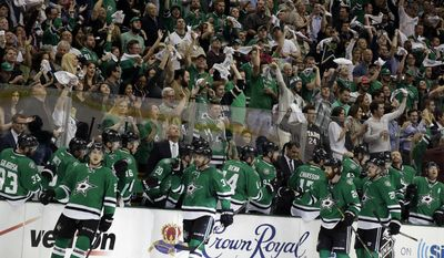 Dallas Stars fans wave rally towels as the Stars bench celebrates a goal by center Vernon Fiddler, second from bottom left, in the second period of Game 4 of a first-round NHL hockey Stanley Cup playoff series against the Anaheim Ducks, Wednesday, April 23, 2014, in Dallas. (AP Photo/Tony Gutierrez)