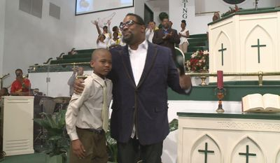 """In an April 10, 2014, image provided by WXIA-TV, 9-year-old Willie Myrick is embraced by Grammy Award-winning gospel singer Hezekiah Walker in front of the congregation at Mt. Carmel Baptist Church in Atlanta.  Police say Myrick was abducted from his driveway but was released after singing the gospel song """"Every Praise"""" until the abductor released him.  (AP Photo/WXIA-TV)"""
