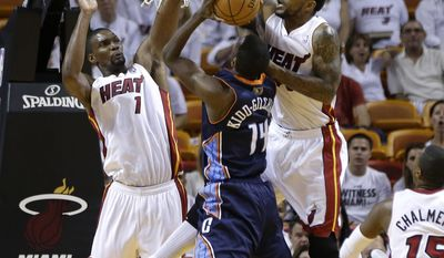 Charlotte Bobcats' Michael Kidd-Gilchrist (14) shoots, and is fouled by Miami Heat's Udonis Haslem, right, as Chris Bosh (1) defends during the first half in Game 2 of an opening-round NBA basketball playoff series, Wednesday, April 23, 2014, in Miami. (AP Photo/Lynne Sladky)