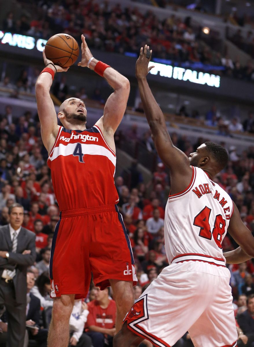 Washington Wizards center Marcin Gortat (4) shoots over Chicago Bulls center Nazr Mohammed (48) during the first half of Game 2 in an opening-round NBA basketball playoff series Tuesday, April 22, 2014, in Chicago. (AP Photo/Charles Rex Arbogast)