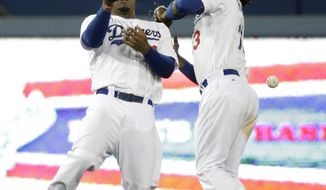 Los Angeles Dodgers' Carl Crawford, left, and Hanley Ramirez misses the ball hit by Philadelphia Phillies' Carlos Ruiz during the 10th inning of a baseball game on Tuesday, April 22, 2014, in Los Angeles. (AP Photo/Jae C. Hong)