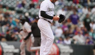 Colorado Rockies relief pitcher Chad Bettis reacts after giving up a grand slam to San Francisco Giants' Hector Sanchez, rear, in the 11th inning of the Giants' 12-10 victory in 11 innings in a baseball game in Denver on Wednesday, April 23, 2014. (AP Photo/David Zalubowski)