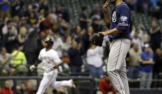 San Diego Padres starting pitcher Tyson Ross, right, waits for a ball as Milwaukee Brewers' Jean Segura rounds the bases after hitting a three-run home run during the second inning of a baseball game on Wednesday, April 23, 2014, in Milwaukee. (AP Photo/Morry Gash)