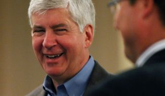 """Michigan Gov. Rick Snyder visits with Trip Johnson, right, during the """"Legislative Luncheon"""" at the Holiday Inn Muskegon Harbor in downtown Muskegon on April 21, 2014. (AP Photo/The Muskegon Chronicle, Ken Stevens)"""