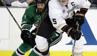 Anaheim Ducks' Ryan Getzlaf (15) controls the puck as he moves away from Dallas Stars' Jordie Benn (24) in the first period of Game 3 of a first-round NHL hockey Stanley Cup playoff series game, Monday, April 21, 2014, in Dallas. (AP Photo/Tony Gutierrez)