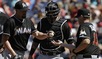 Miami Marlins pitcher Mike Dunn, left, is relieved by manager Mike Redmond, right, in the eighth inning of a baseball game against the Atlanta Braves, Wednesday, April 23, 2014, in Atlanta. (AP Photo/David Goldman)