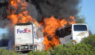 FILE - In this Thursday, April, 10, 2014, file photo, massive flames engulf a tractor-trailer and a tour bus just after they collide on Interstate 5, near Orland, Calif. The mother of a 17-year-old honors student who was among 10 people killed in the fiery Northern California bus crash sued FedEx on Tuesday, April 22, 2014, alleging that its trucks have a history of catching fire. (AP Photo/Jeremy Lockett, File)