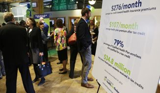 A chart showing the average premium cost and tax credit data for people who enrolled in the Washington state healthcare exchange is shown at an event Wednesday, April 23, 2014 in Seattle to highlight the success of the Washington state healthcare exchange in getting hundreds of thousands of people into new health coverage, including about 450,000 who obtained new Medicaid coverage. (AP Photo/Ted S. Warren)