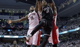 Brooklyn Nets forward Paul Pierce (34) drives to the basket against Toronto Raptors forward Amir Johnson (15) during the second half of Game 2 in an NBA basketball first-round playoff series, Tuesday, April 22, 2014, in Toronto. Toronto won 100-95. (AP Photo/The Canadian Press, Frank Gunn)
