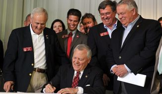Surrounded by bill supporters, Georgia Gov. Nathan Deal signs House Bill 60 into law during a signing event Wednesday, April 23, 2013, in Ellijay, Ga. The bill makes several changes to the state's gun law. It allows those with a license to carry to bring a gun into a bar without restriction and into some government buildings that don't have certain security measures. It also allows religious leaders to decide whether it's OK for a person with a carry license to bring a gun into their place of worship. (AP Photo/Atlanta Journal-Constitution, Brant Sanderlin)  MARIETTA DAILY OUT; GWINNETT DAILY POST OUT; LOCAL TV OUT; WXIA-TV OUT; WGCL-TV OUT