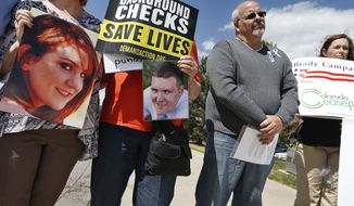 Tom Sullivan, second from right, who's son Alex was killed in the 2012 Aurora movie theatre massacre, attends a rally against gun violence in front of Republican Congressman Mike Coffman's office, in Aurora, Colo., Wednesday April 23, 2014. Sullivan and other parents of Aurora theater shooting victims urged Coffman to support universal background checks in Congress. (AP Photo/Brennan Linsley)