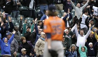 Seattle Mariners fans cheer as Houston Astros closing pitcher Josh Fields heads off the field after giving up a walk-off home run to Seattle Mariners' Kyle Seager in the ninth inning of a baseball game Wednesday, April 23, 2014, in Seattle. The Mariners won 5-3. (AP Photo/Elaine Thompson)