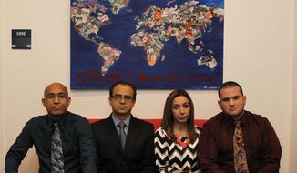 REMOVES SENTENCE THAT SAYS THE TEACHERS LOST THEIR JOBS AND RESIDENCY STATUS AND CLARIFIES PROGRAM'S STATUS - In this photo taken on March 13, 2014, from left, Alfonso Casares Tafur, Bernardo Montes-Rodriguez, Elizabeth Nino de Rivera, and Francisco Javier Marcano pose for a photo at the offices of SMU's Embrey Human Rights Program in Dallas. They are among the teachers recruited under Garland Independent School District's H-1B visa program, which is now under federal investigation. (AP Photo/The Dallas Morning News, Evans Caglage)  MANDATORY CREDIT; MAGS OUT; TV OUT; INTERNET USE BY AP MEMBERS ONLY; NO SALES