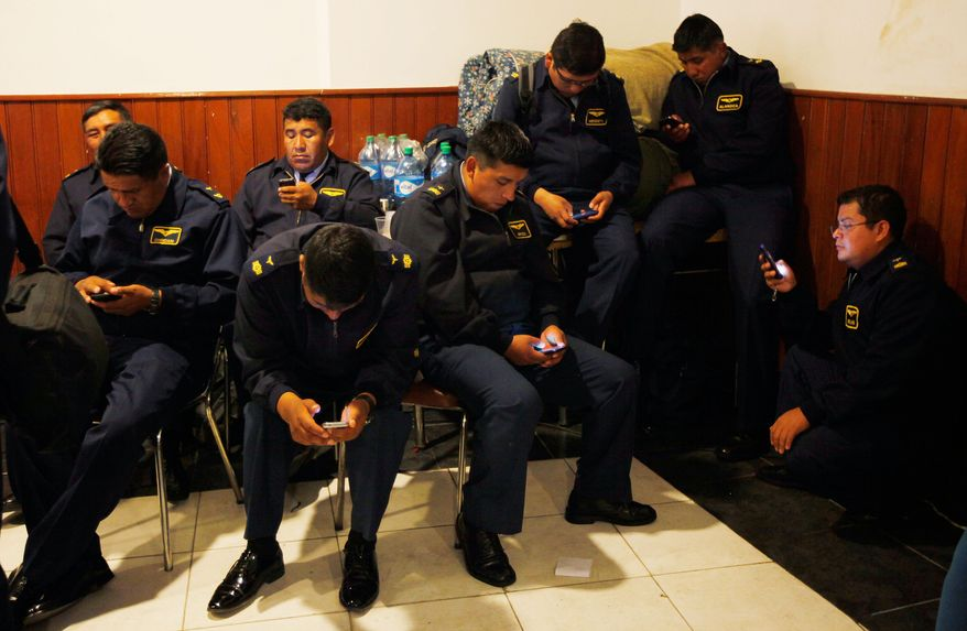 Air Force members check their cell phones after protesting for a second day, as they rest at the headquarters of the National Association of Warrant Officers and Sergeants in La Paz, Bolivia, Wednesday, April 23, 2014. Hundreds of low ranking soldiers from Bolivia's Armed Forces marched for a second day against the military high command's dismissal of four of its leaders who defended their call for more career opportunities. The Ministry of Defense has threatened to discharge the soldiers who continue to protest. (AP Photo/Juan Karita)