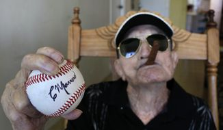 **FILE** In this April 23, 2013 photo, Cuba's former pitcher Conrado Marrero, the world's oldest living former major league baseball player, holds up a baseball with his signature at his home, two days before is 102nd birthday, as he holds an unlit cigar in his mouth in Havana, Cuba. (AP Photo/Franklin Reyes)