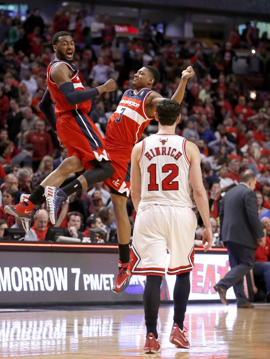 Washington Wizards guard John Wall, left, and Bradley Beal celebrate the Wizards' 101-99 win as Chicago Bulls guard Kirk Hinrich walks off the court after missing two free throws during the overtime period of Game 2 in an opening-round NBA basketball playoff series Tuesday, April 22, 2014, in Chicago. (AP Photo/Charles Rex Arbogast)