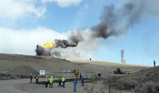 This image provided by Rachel Anderson shows officials at the site of an explosion and fire at a natural gas processing facility and major national pipeline hub, Wednesday, April 23, 2014, in Opal, Wyo. Officials said there are no reports of injuries and the residents of Opal have been evacuated to an area about 3 miles outside the town as a precaution. Opal has about 95 residents and is about 100 miles northeast of Salt Lake City. (AP Photo/Rachel Anderson)