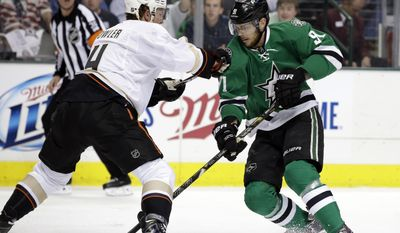 Anaheim Ducks' Cam Fowler (4) defends as Dallas Stars' Tyler Seguin (91) moves the puck up ice in the first period of Game 4 of a first-round NHL hockey Stanley Cup playoff series, Wednesday, April 23, 2014, in Dallas. (AP Photo/Tony Gutierrez)