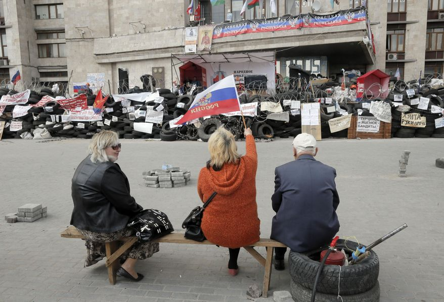 Pro-Russian activists with Russian flag sitting at a barricade at the regional administration building in Donetsk, Ukraine, Wednesday, April 23, 2014.    Pro-Russian gunmen in eastern Ukraine said on Wednesday that they are holding captive American journalist with Vice News Simon Ostrovsky who has not been seen since early Tuesday April 22.  Ostrovsky has been covering the crisis in Ukraine for some weeks and was reporting about groups of masked gunmen seizing government buildings in eastern Ukrainian. (AP Photo/Efrem Lukatsky)