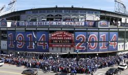Baseball fans wait to enter Wrigley Field on the 100th anniversary of the first baseball game at the ballpark, before a game between the Arizona Diamondbacks and Chicago Cubs, Wednesday, April 23, 2014, in Chicago. (AP Photo/Charles Rex Arbogast)